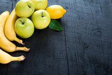 Apples, Bananas And Lemon On Black Background