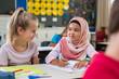 Leinwanddruck Bild - Muslim girl with her classmate