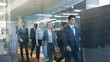 Diverse Team of Delegates/ Lawyers Confidently Marching Through the Corporate Building Hallway. Multicultural Crowd Of Resolute Business People in Stylish Marble and Glass Offices.