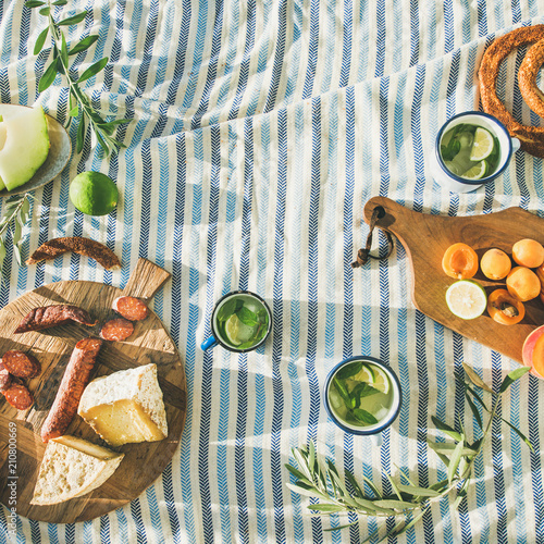 Keuken foto achterwand Picknick Flat-lay of summer picnic set with fruit, cheese, sausage, bagels and lemonade over striped blanket, top view, copy space, square crop