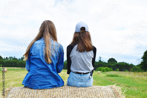 a04976a317 Two girls wearing jeans sitting on big straw roll on green field outside in  cloudy summer