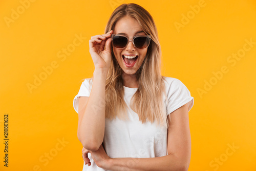 Fotografiet Portrait of an excited young blonde girl in sunglasses