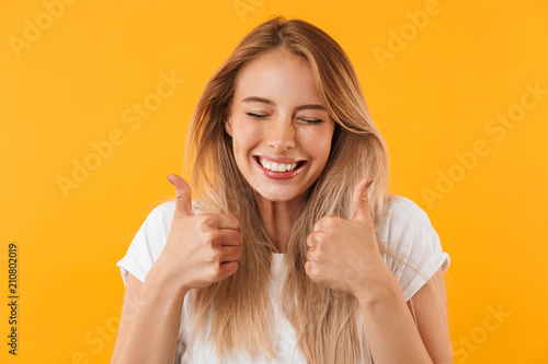 Portrait of a joyful young girl showing two thumbs up