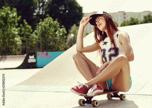 Beautiful young sexy girl sits on a skateboard in short green shorts, red sneake Canvas-taulu