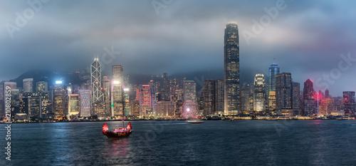 Panorama der Skyline von Hong Kong am Abend mit bewölktem Himmel