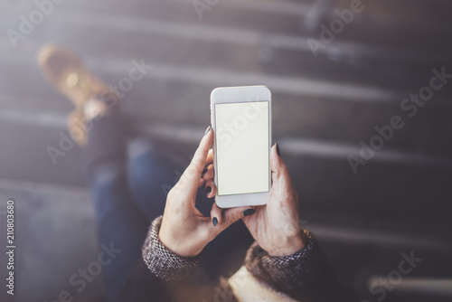 Woman holding hands smartphone and texting message.Female hands using mobile phone.Closeup on blurred background.Flares, bokeh effects. Mock-up.