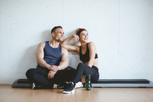 Athlete Couple Smiling After Good Workout In Gym. Sporty Gym Concept