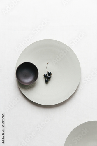 Black currants on a plate on a white surface. - 210813883