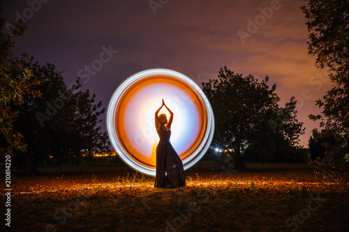Female silhouette in glowing circle in nature