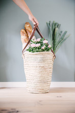 A Woman Hand Holding A Rush Or Wicker Basket With Light Pink Roses, With Two Baguettes And A Couple Of Leeks.