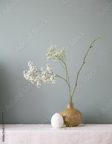 Foto op Canvas Bloemen A floral setting with ceramic vases filled with baby's breath and a linden branch on a white table top against a muted grey green wall.