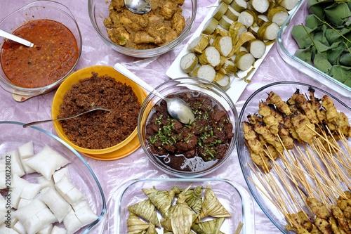 Foto 'Kuah Kacang' or  peanut sauce, chicken satay, Ketupat Daun Palas or malay rice dumpling, lemang, rendang  and fermented sticky rice