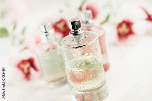 Photo  Spray bottle of floral feminine perfume closeup, soft light and focus, fresh drops on glass, delicate light dreamy background flower decor, pastel colors, diagonal