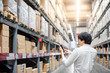 Young Asian man checking the shopping list on his smartphone between product shelves. warehouse shopping lifestyle concept