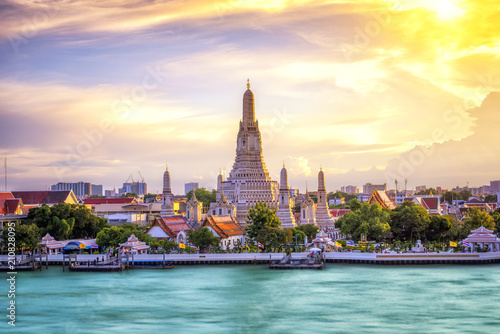 Photo Stands Bangkok Thai Temple at Chao Phraya River Side, Sunset at Wat Arun Temple in Bangkok Thailand. Wat Arun is a Buddhist temple in Thon Buri District of Bangkok, Thailand, Wat Arun is among the best known of Thai