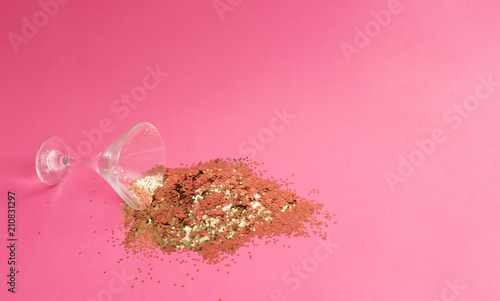 Spilled martini glass full of gold glitter on pink background. Creative minimal party concept. - 210831297