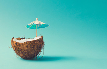 Tropical beach concept made of coconut fruit and sun umbrella. Creative minimal summer idea.
