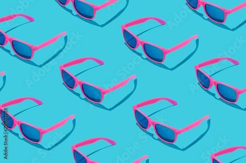 Fotografia  Pink sunglasses pattern on pastel blue background