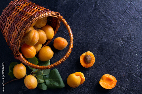 Delicious ripe apricots in a basket on black background, close-up, space for text. View from above, top studio shot