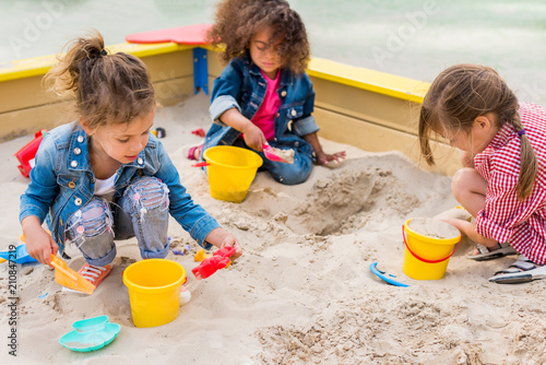 Obraz na plátně three multiethnic little children playing with plastic scoops and buckets in san