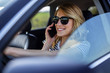 Woman speaks on the phone in the car.