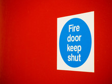 Fire Door Keep Shut Sign On A Red Door