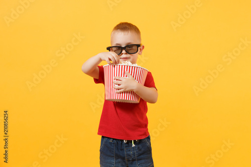 Платно Little cute kid baby boy 3-4 years old in red t-shirt, 3d imax cinema glasses holding bucket for popcorn, eating fast food isolated on yellow background