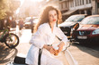 Beautiful lady with dark curly hair in white costume sitting on white moped with cup of coffee to go and thoughtfully looking in camera on street