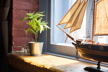 Model Of A Boat And Flower In A Pot On A Wooden Window Sill In An Old House