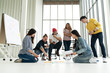 canvas print picture - Young creative diverse group meeting and looking at project plan lay out on floor discuss or brainstorm business strategy with post note. Workshop for startup team in modern office. Happy workplace.
