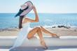 canvas print picture - Frau sitzt in der Sonne an einem Strand in Griechenland