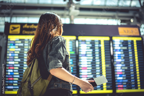 Beauty female tourist looking at flight schedules for checking take off time Fototapeta