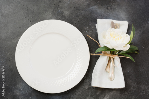 Romantic dinner. Table setting with white peony on black table. Top view.