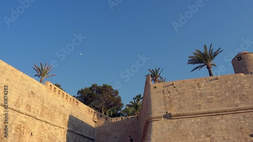 Walls and castle view outdoors and the moon on the background. Old town in Peniscola, Spain. Golden hour time of day.