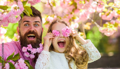 Father and daughter on happy face play with flowers as glasses, sakura background. Child and man with tender pink flowers in beard. Girl with dad near sakura flowers on spring day. Family time concept