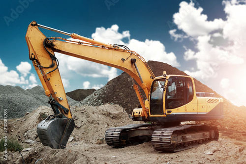 Fotografia Excavator at the construction site, sand, crushed stone, against the blue sky background