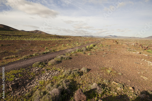 Deurstickers Landschap Dirt road through volcanic landscape, La Caldera de Gairia, Fuerteventura, Canary islands, Spain