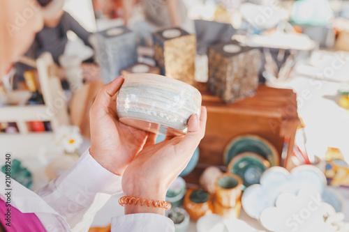 Fotografía woman selecting ceramic tableware in the flea market