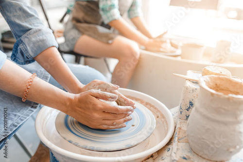 Fotografija Top view of hands with clay making of a ceramic pot on the pottery wheel, hobby