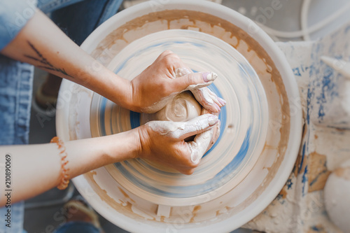 Slika na platnu Top view of hands with clay making of a ceramic pot on the pottery wheel, hobby