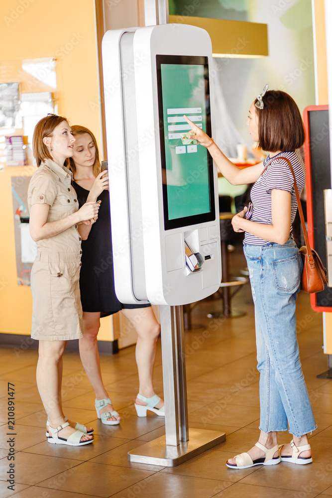 Fototapeta Group of people, friends ordering food at the touch screen self service terminal by the electronic menu in the fastfood restaurant