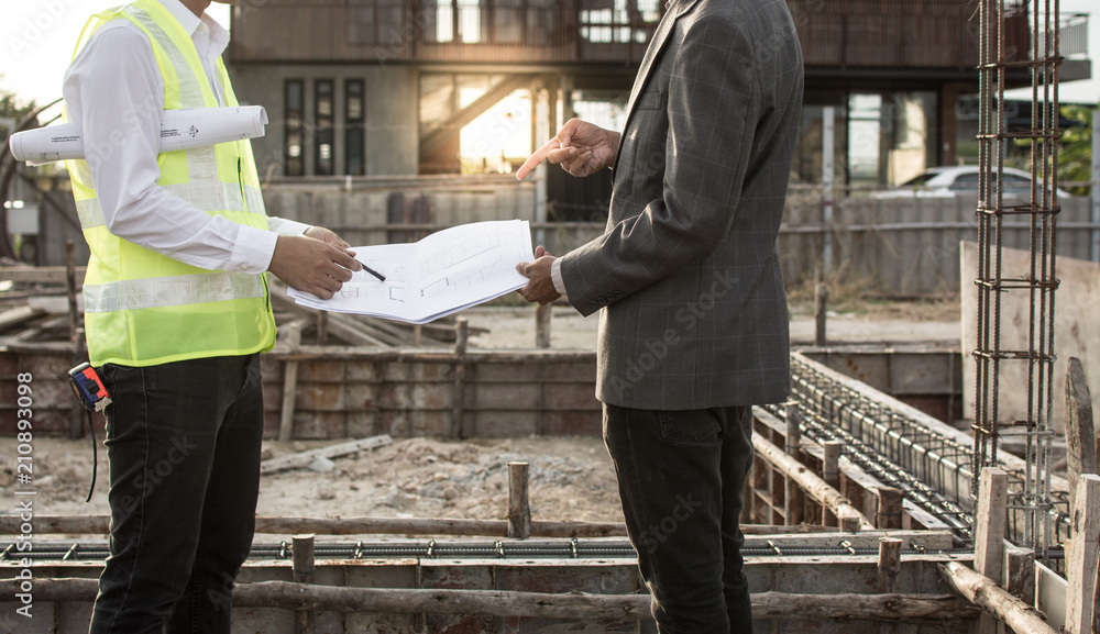 Fototapeta Engineer and Architect working at Construction Site