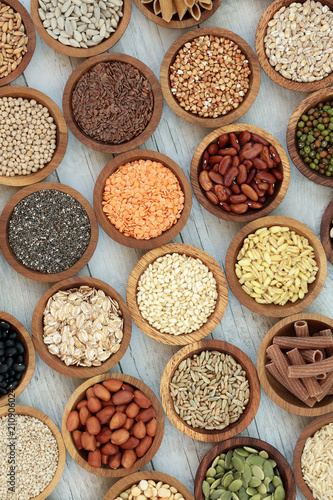 Poster Assortiment Dried macrobiotic super food with legumes, seeds, nuts, cereal, grains, vegetables & whole wheat pasta with foods high in protein, omega 3, anthocyanins, antioxidants, minerals & vitamins. Top View.