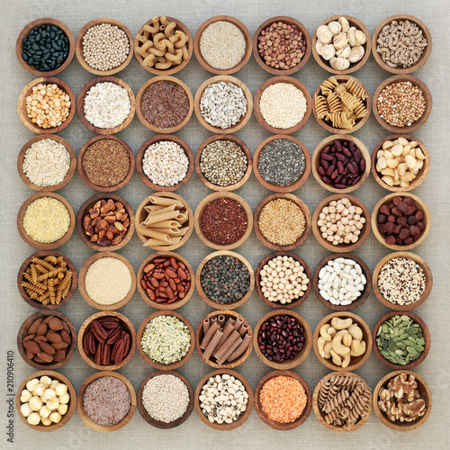 Poster Assortiment Vegan high protein dried health food with nuts, seeds, legumes, whole wheat pasta, grains & cereals. Foods high in fibre, antioxidants, anthocyanins, vitamins & minerals. Top view on hessian.