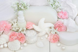 Bridal spa and beauty treatment and cleansing products with carnation flowers, ex foliating salt, seashell soaps, body lotion, sponges, wash cloths with decorative shells and pearls on white wood.