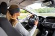 Junge Frau mit verbundenen Augen am Steuer eines Autos