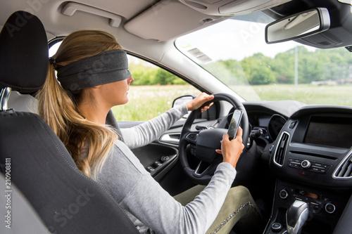 Fotografia  Junge Frau mit verbundenen Augen am Steuer eines Autos