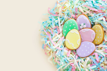 Fototapeta na wymiar Easter homemade gingerbread cookie. Bird's nest Easter made from colored paper. Beige background.