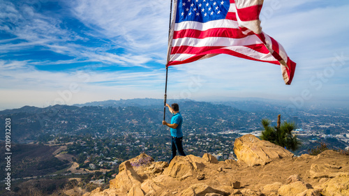 Man waves American flag above Los Angeles at Hollywood Sign Wallpaper Mural
