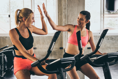 Spoed Foto op Canvas Fitness Attractive young women working out together on exercise bike at the gym.